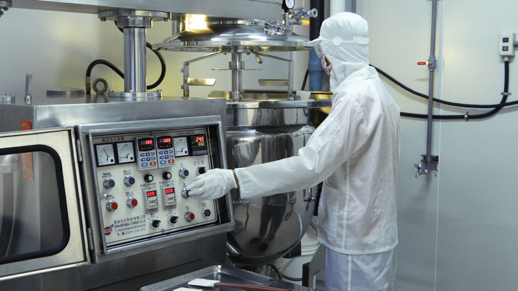 Technician in the factory at the creams mixing station